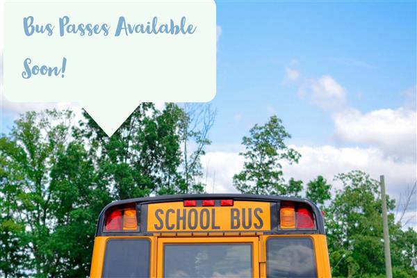 A school bus with a sky and trees in the background with text saying Bus Passes Available Soon!